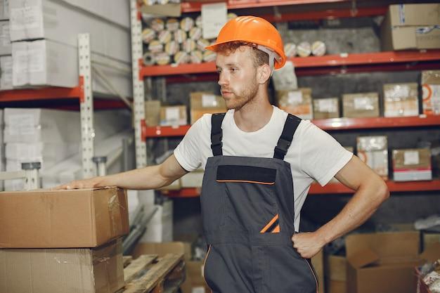 Industriearbeiter drinnen in der fabrik. junger techniker mit orangefarbenem schutzhelm.