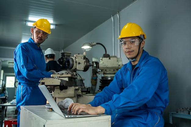 Industriearbeiter mit einem laptop, der in der fabrik arbeitet.