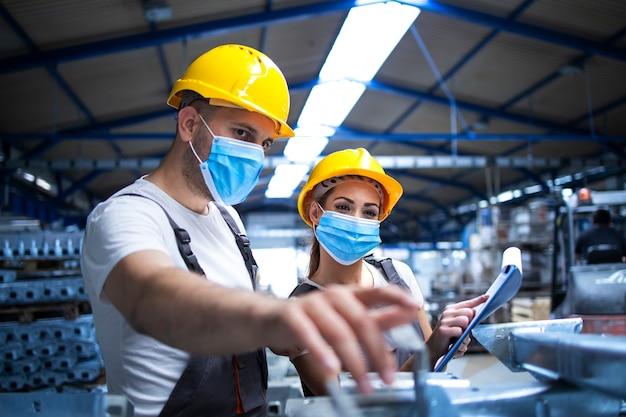 Industriearbeiter mit gegen das koronavirus geschützten gesichtsmasken diskutieren über metallteile in der fabrik