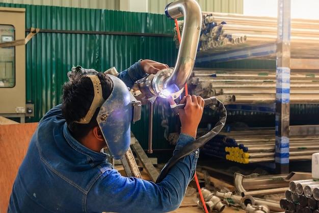 Industriearbeiter mit schutzmaske, die metallrohrleitung unter verwendung des schweißers schweißt