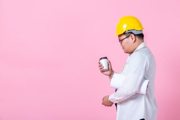 Industriearbeiter oder ingenieur, der einen architekten-baumeister arbeitet, der den layout-plan studiert, ernsthafter bauingenieur, der eine tasse kaffee hält und mit dem lesen auf blaupausen arbeitet, die auf rosa leerem kopierraum-studio isoliert sind?