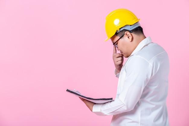 Industriearbeiter oder ingenieur, der einen architekten-baumeister arbeitet, der den layoutplan studiert, ernsthafter bauingenieur, der mit dem lesen auf blaupausen arbeitet, isoliert auf rosa leerem kopienraum studiohintergrund, innenstudio?