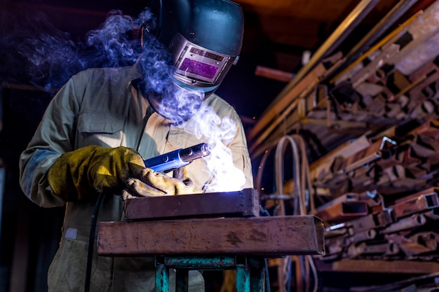 Industriearbeiterarbeiter an der fabrik, die stahlkonstruktion mit schutzmaske und uniform schweißt.