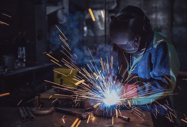Industriearbeiterarbeiter an der fabrik, die stahlkonstruktion schweißt
