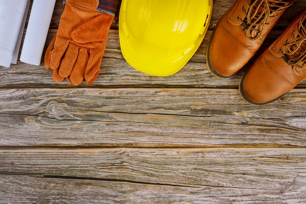 Industriearbeiterarchitekt mit blaupausen in der büroansicht stellte schutzarbeitskleidung-arbeitsstiefel auf gelbem schutzhelm ein