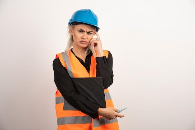 Industriearbeiterin der frau, die zwischenablage auf weißem hintergrund hält. hochwertiges foto