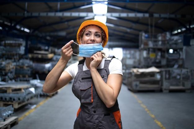 Industriearbeiterin, die in der fabrikhalle steht und eine hygienemaske auf das gesicht setzt, um sich vor hoch ansteckendem koronavirus zu schützen