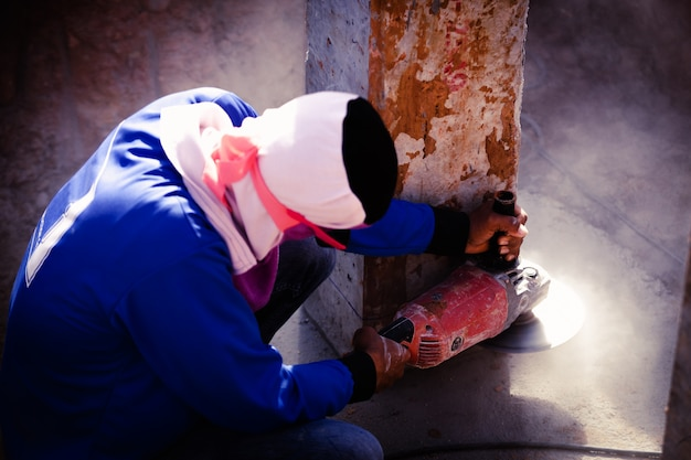 Industriebauarbeiter-arbeiter, die elektrisch hält, sah den beton schneiden
