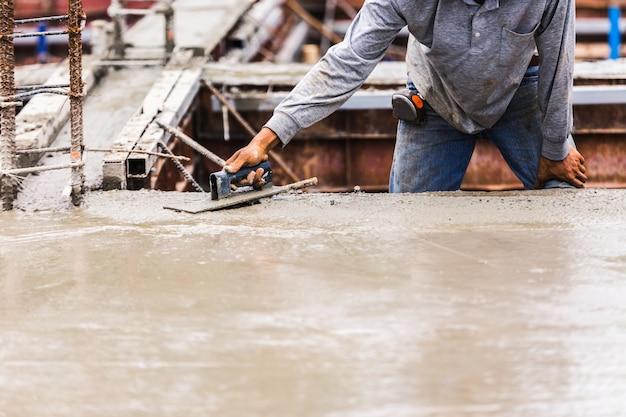 Industriebaumännerarbeitskräfte mit konkreter mischung des werkzeugs auf bodenbau