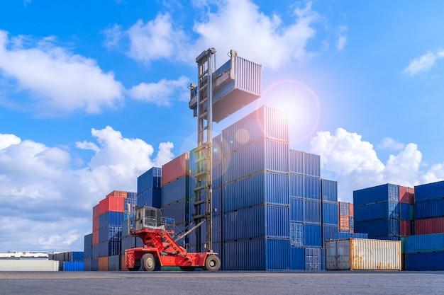Industriecontainerhof für logistischen import exportgeschäft, gabelstapler, der frachtversandcontainerbox im logistischen versandhof mit frachtcontainerstapel abwickelt