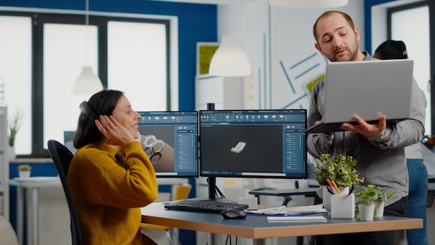 Industriedesigner diskutieren mit ingenieurin, die pc anschaut