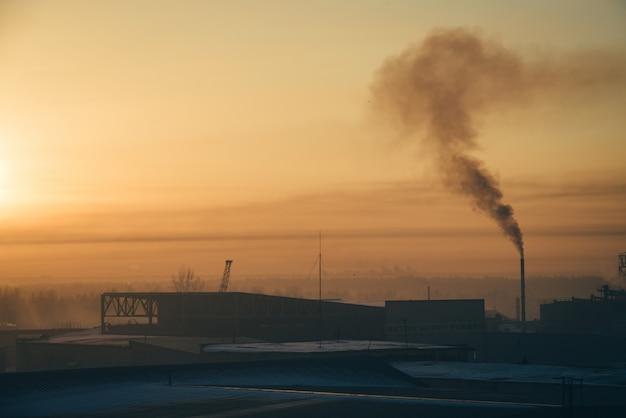 Industriegebäude bei sonnenaufgang. lagerhäuser. rauch aus dem rohr.