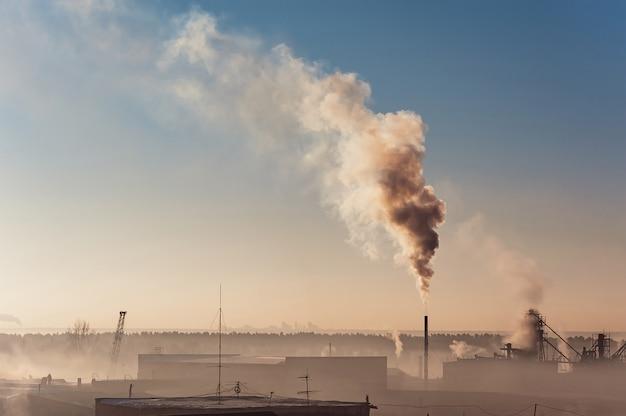 Industriegebäude im nebel am blauen himmel. lagerhäuser. rauch aus dem rohr. smog.
