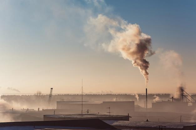 Industriegebäude im nebel am blauen himmel. lagerhäuser. rauch aus dem rohr.