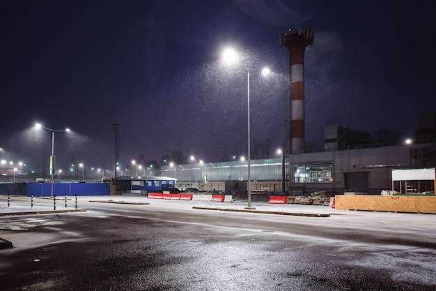 Industriegebiet am stadtrand bei nacht. straßenlaternen beleuchten den schnee, der von oben fällt.