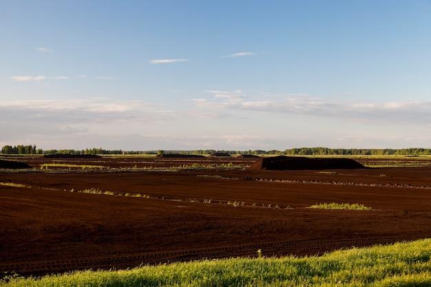 Industriegebiet, in dem bergbau in schwarztorf betrieben wird. foto mit geringer schärfentiefe. sommersaison, blauer himmel im hintergrund