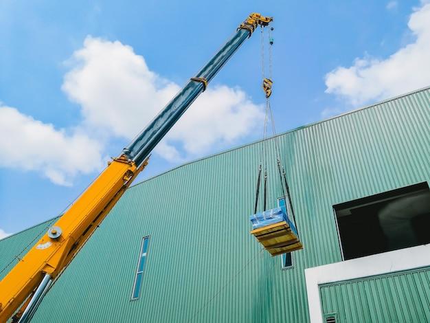 Industriekran, der ein maschinenteil gegen sonnenlicht und blauen himmel betreibt und anhebt
