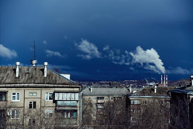 Industrielandschaft des metallurgischen stadtwerks. wohngebäude, rauchende pfeifen auf einem hintergrund des blauen himmels