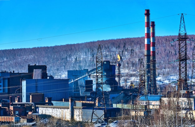 Industrielandschaft - die fackel einer kokereianlage erzeugt thermische emissionen in die atmosphäre vor dem hintergrund einer winterlandschaft