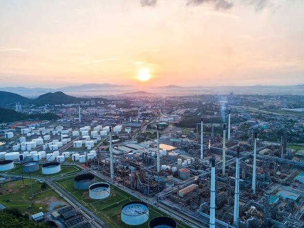 Industrielle ansicht an der erdölraffineriebetriebsformular-industriezone mit sonnenaufgang und bewölktem himmel.