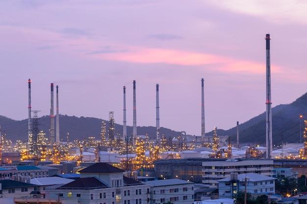 Industrielle ansicht an der erdölraffineriebetriebsformular-industriezone mit sonnenuntergang und bewölktem himmel