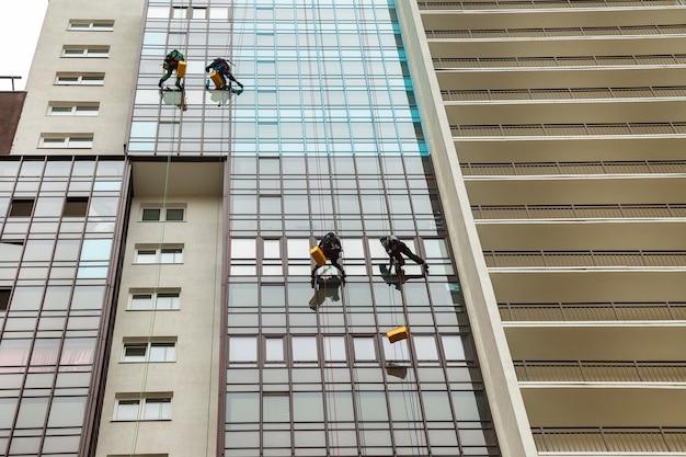 Industrielle bergsteiger hängen über wohnfassadengebäude, während sie die außenfassadenverglasung waschen. seilzugangsarbeiter hängt an der hauswand. konzept der städtischen arbeiten der industrie. platz kopieren