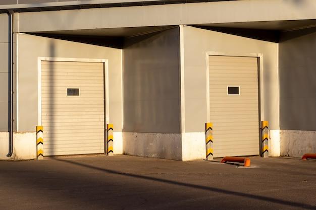 Industrielle graue einheitsfassade des lagerhauses mit geschlossenen weißen metalltortüren bei sonnenuntergang