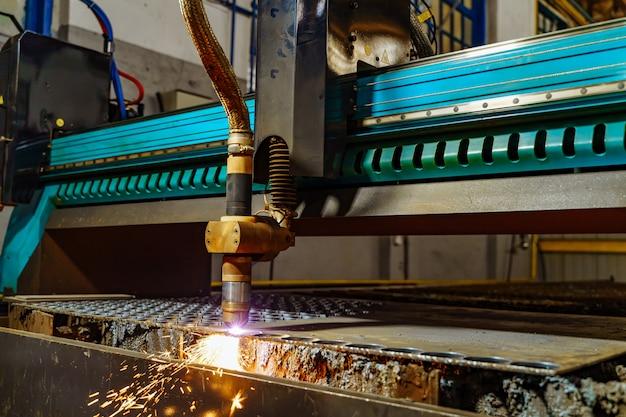 Industrielle laserschneidbearbeitung fertigungstechnologie aus flachblech stahlmaterial. spezieller laserschneider mit funken.