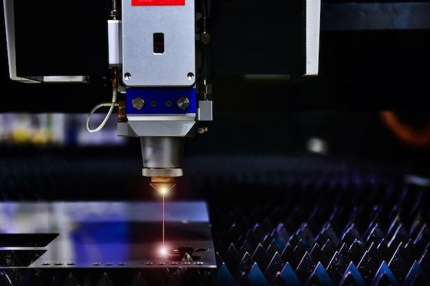 Industrielle laserschneidmaschine beim schneiden des blechs mit dem funkenlicht