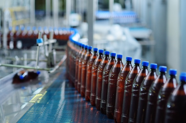 Industrielle lebensmittelproduktion von bier. plastikbierflaschen auf einem förderband im hintergrund einer brauerei