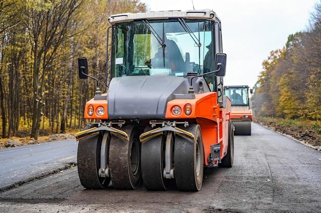 Industrielle pflastermaschine, die neuen frischen asphalt legt. frischer asphalt auf der autobahnbaustelle.