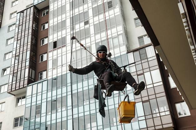 Industrieller bergsteiger hängt über wohnfassadengebäude, während er die außenfassadenverglasung wäscht. seilzugangsarbeiter hängt an der hauswand. konzept der städtischen arbeiten der industrie. platz kopieren