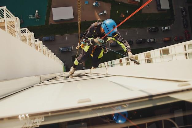 Industrieller bergsteiger hängt über wohnfassadengebäude, während er die außenfassadenverglasung wäscht. seilzugangsarbeiter hängt an der hauswand. konzept der städtischen werke. platz für website kopieren