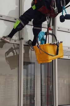 Industrieller bergsteiger hängt über wohngebäude, während er die außenfassadenverglasung wäscht. seilzugangsarbeiter hängt an der hauswand. konzept der städtischen werke. platz kopieren