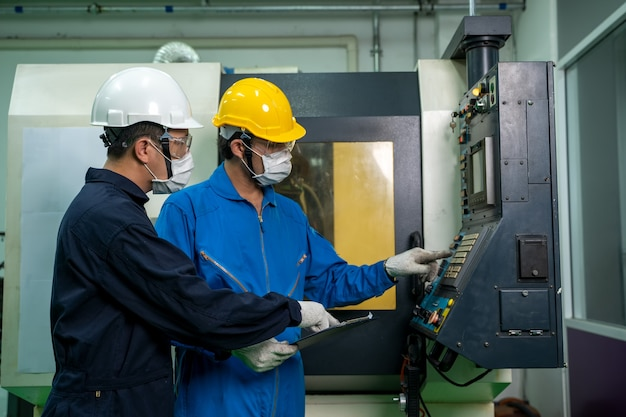 Industrieller fabrikangestellter, der in der nähe der stromzählertafel eines kontrollraums arbeitet und prüft.