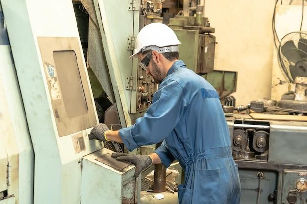 Industrieller fabrikangestellter, der mit maschinen arbeitet