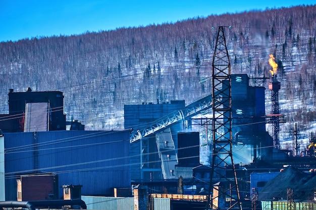 Industrieller hintergrund - die fackel einer kokereianlage erzeugt thermische emissionen in die atmosphäre vor dem hintergrund einer winterlandschaft