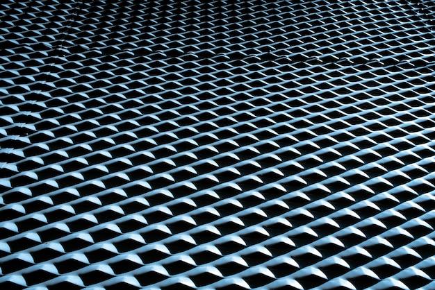 Industrieller hintergrund mit der metallischen beschaffenheit belichtet mit starkem licht und intensiven schatten und sich wiederholendem muster.