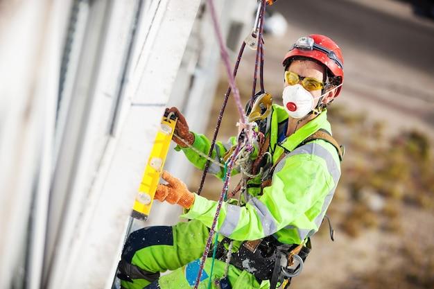 Industrieller kletterer, der während der überwinterungsarbeiten mit einem nivellierrohr misst