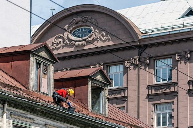 Industrieller kletterer entfernt blätter und schmutz von der regenrinne auf dem dach des hauses