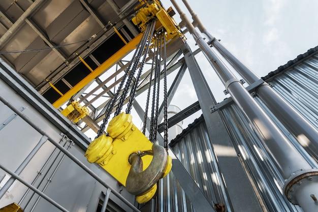 Industrieller laufkran mit kette und großem gelben haken im werk. hebemechanismus