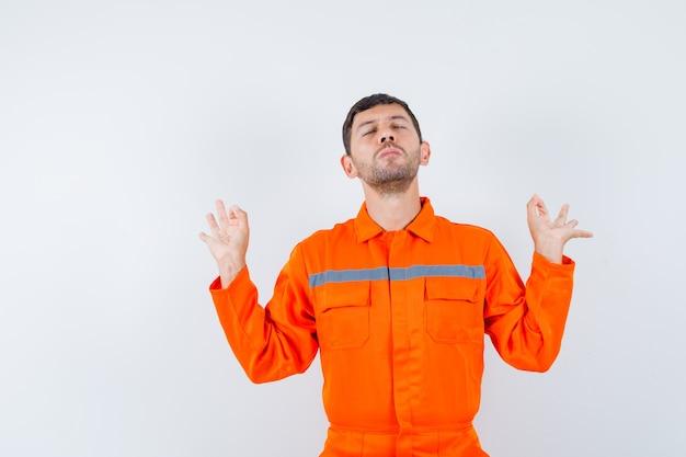 Industrieller mann, der meditation mit geschlossenen augen in uniform tut und friedlich, vorderansicht schaut.