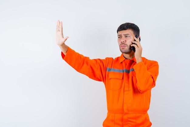 Industrieller mann in der uniform, die auf handy spricht und stoppgeste, vorderansicht zeigt.