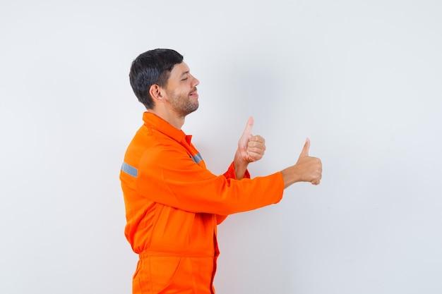 Industrieller mann in der uniform, die doppelte daumen hoch zeigt und fröhlich aussieht.