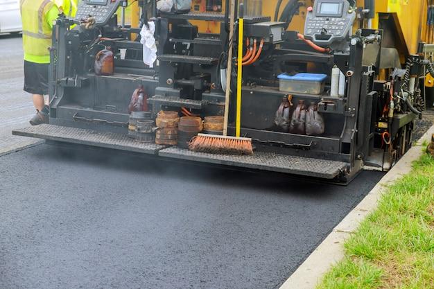 Industrieller pflasterwagen, der frischen asphalt auf baustelle legt