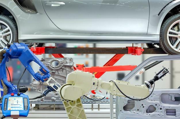 Industrieller roboter, der mit autoteilen auf unscharfem kontrollhintergrund arbeitet.