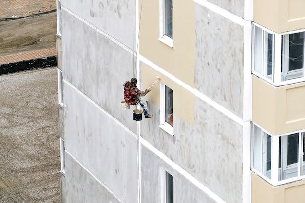 Industrieller seilzugangsarbeiter, der vom gebäude hängt, während er die außenfassadenwand streicht. konzeptbild des industriellen alpinismus.