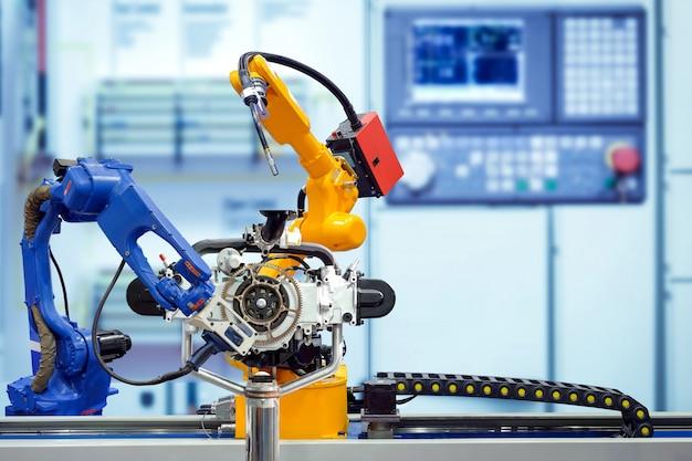 Industrielles roboterschweißen und roboterscan 3d, der mit motorteilen auf intelligenter fabrik arbeitet.