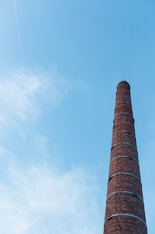 Industrielles rohr des ziegelsteines gegen den himmel.