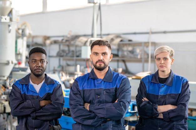Industriemanager bespricht die produktion mit arbeitern, während er daten auf dem tablet analysiert und über die werkstatt geht
